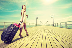 Young woman walking with suitcase on wheels Royalty Free Stock Photos