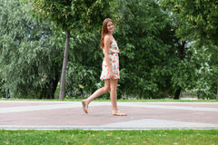 Young woman walking on the summer park Stock Images