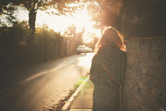 Young woman walking into sunset in city Stock Photos