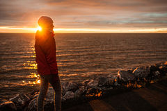 Young Woman Walking during Sunset on a Cold Evening. Young Woman Walking on the Beach during Sunset on a Cold Evening stock image