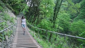 Young woman is walking on a suspension bridge in a forest in the mountains stock footage