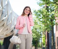 Young woman walking and talking on mobile phone Stock Photography