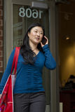 Young woman walking and talking on the phone Stock Photography