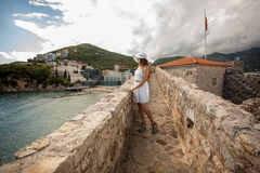 Young woman walking on top of stone wall at old castle Royalty Free Stock Photos