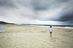 Young woman walking toward the coastline Stock Image