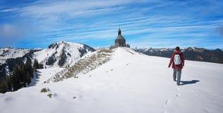 Young woman walking towards mountain chapel in snowy landscape Stock Image