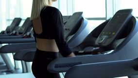 Young woman is walking on a treadmill in the gym. Young sports woman is walking on a treadmill in the gym stock video