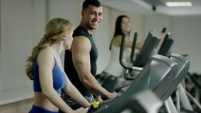 Young woman walking on treadmill and speak to young man stock footage