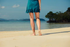 Young woman walking on tropical beach Stock Images