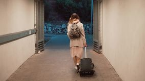 Young woman walking through tunnel carrying the suitcase. Girl with backpack walking the city, traveling. Slow motion. stock footage