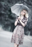Young woman walking with umbrella. Soft white colors Stock Photo