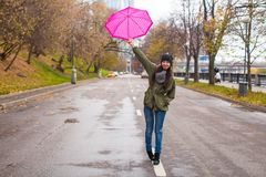 Young woman walking with umbrella in autumn rainy Royalty Free Stock Photos