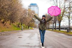 Young woman walking with umbrella in autumn rainy. Day. This image has attached release Stock Photos