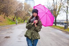 Young woman walking with umbrella in autumn rainy. Day. This image has attached release Stock Images