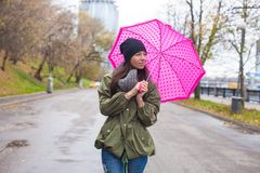 Young woman walking with umbrella in autumn rainy Royalty Free Stock Images