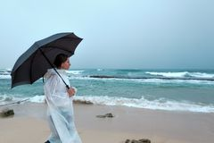Young woman walking with an umbrella in front of ocean in rainy weather. Enjoy rain in vacation Stock Photography