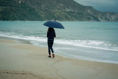 Young woman walking with an umbrella in front sea in winter or a. Utumn Royalty Free Stock Image