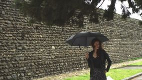 Young woman walking under an umbrella in the Park along the stone wall. Young woman walking under an black umbrella in the Park along the stone wall stock video