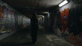 Young Woman Walking in an Underground Passageway 2. A young woman casually walks in an underground passageway with her back turned away from the camera. The stock video footage