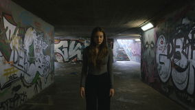 Young Woman Walking in an Underground Passageway 2. A young woman casually walks in an underground passageway towards the camera. The underground passageway is stock video