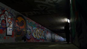 Young Woman Walking Beside an Underpass Wall. A young woman walking beside an underpass wall. The underground passageway is spray painted all over, and stock video