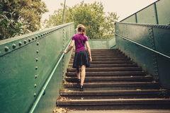 Young woman walking up stairs. A young woman is walking up stairs outside in a park Stock Photography