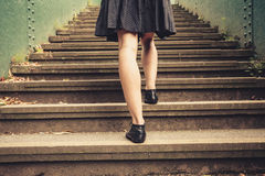 Young woman walking up stairs. A young woman is walking up stairs outside in a park Royalty Free Stock Images