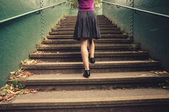 Young woman walking up stairs. A young woman is walking up stairs outside in a park Stock Photos