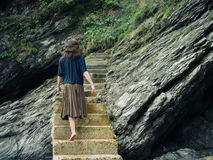 Young woman walking up steps by cliff Stock Image