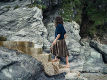 Young woman walking up steps by cliff Royalty Free Stock Images