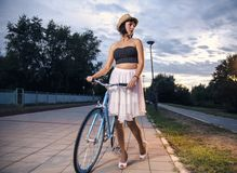 Young woman walking with vintage blue bicycle Stock Photos