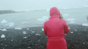 Young woman walking through the volcanic black beach to man in raincoat standing alone on the shore. Cold rainy day. stock video