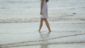 Young woman walking in the water at the beach in slow motion stock footage