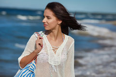 Young woman walking in water wearing white beach  dress Stock Photo
