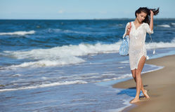 Young woman walking in water wearing white beach  dress Royalty Free Stock Photo