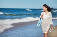 Young woman walking in water wearing white beach  dress Royalty Free Stock Images