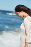 Young woman walking in water wearing white beach  dress Stock Photography