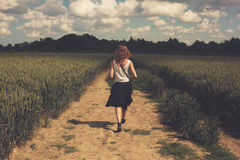 Young woman walking in a wheat field Stock Photo