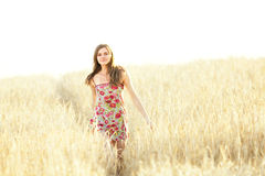 Young woman walking in wheat field Stock Photo