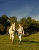 Young woman walking on a white horse at the ranch Royalty Free Stock Photo