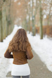 Young woman walking in winter park. rear view Royalty Free Stock Images