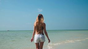 Young woman in jeans shorts walking at shallow tropical sea. Young Woman Walkng at Shallow Tropical Sea shot with a Sony a6300 fps29,97 FHD stock video
