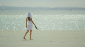 Young woman walks along the beach in slow motion stock video