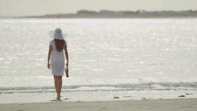 Young woman walks along the beach in slow motion stock footage