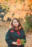 A young woman walks in the autumn Park. Brunette woman wearing a green coat. stock image