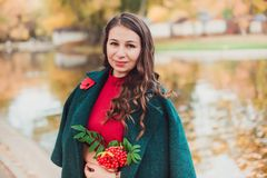 A young woman walks in the autumn Park. Brunette woman wearing a green coat and red dress stock photo