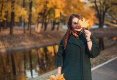 A young woman walks in the autumn Park. She stands by the lake. Brunette woman wearing a green coat stock photos