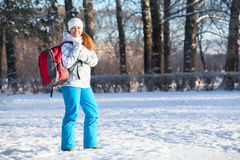 Young woman walks with backpack in winter park, copyspace Stock Photo