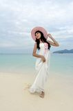Young woman walks on beach Stock Images