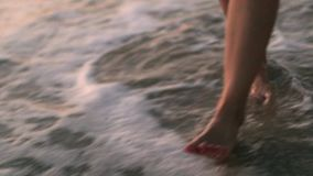 Young woman walks on the beach. Young woman relaxing at sunset and walks near sea on the beach in Dubai stock video footage
